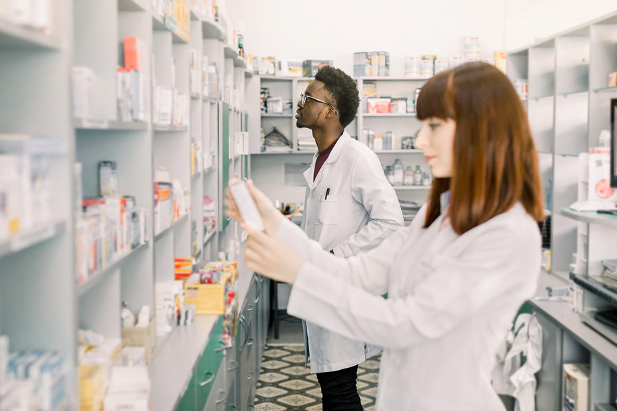 Two Young Multiethnical Pharmacists Working At Modern Pharmacy.